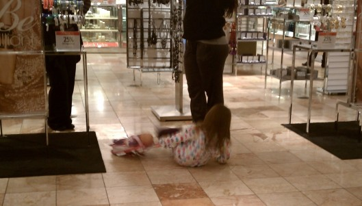 Child in Macy's throwing her baby doll around