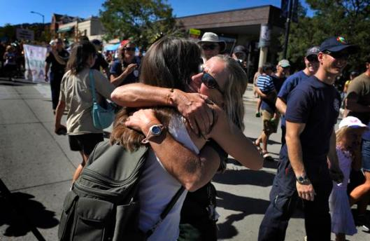 Spice Jones, left, gives Melanie Pray, a firefighter with the Boulder Rural Fire Protection District, an emotional hug Sunday on the Pearl Street Mall in Boulder during a parade to thank the local crews that fought the Fourmile Canyon fire. ( Judy DeHaas, The Denver Post )